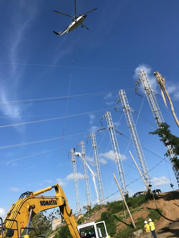 Photo -  A helicopter lifts a power line for Cobra Acquisitions crew members as they work to restore power to Puerto Rico. Cobra Acquisitions is a subsidiary of Oklahoma City-based Mammoth Energy Services Inc. [Photo provided]