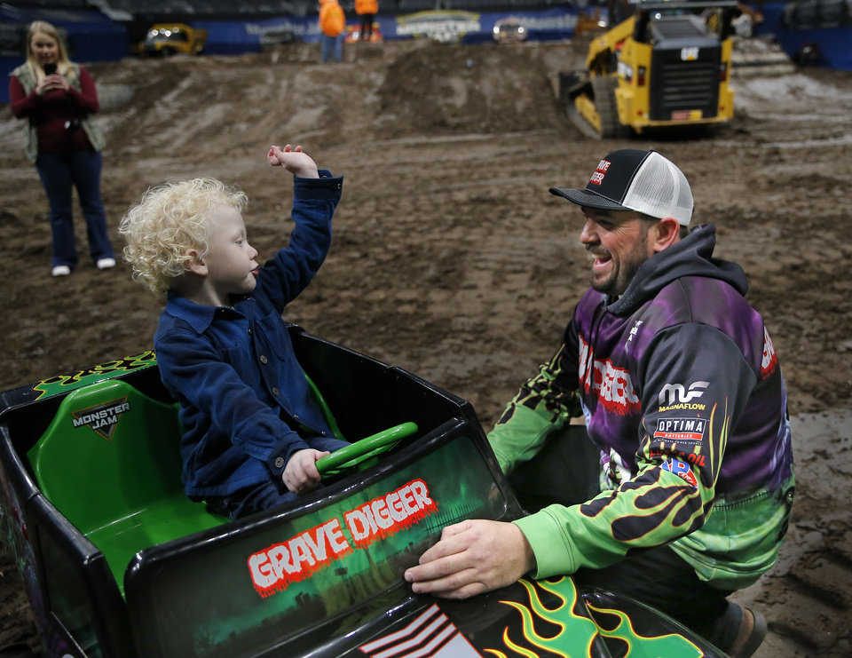 Photo - Monster Jam driver Grave Digger, Brandon Vinson, helps Ryker Ammons, 4, of Yukon, Okla., around the track at Chesapeake Energy Arena in Oklahoma City, Friday, Feb. 14, 2020.  [Sarah Phipps/The Oklahoman]