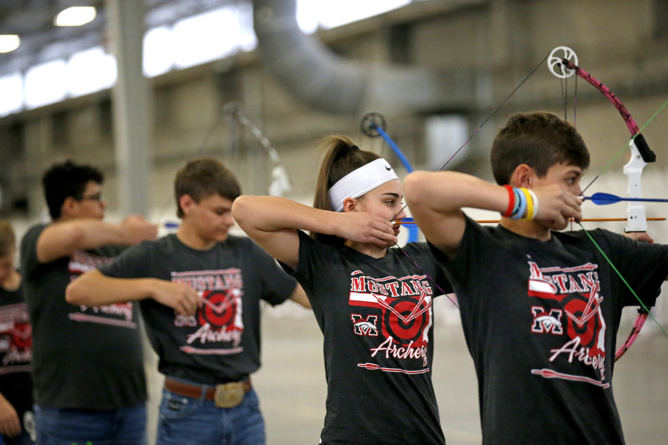Photo -  ABOVE: Students from Mustang Middle School compete Wednesday during the Western Tier 2 Oklahoma State Archery in the Schools Program and Varsity Archery competition at The Pavilion at the OKC State Fair Park.