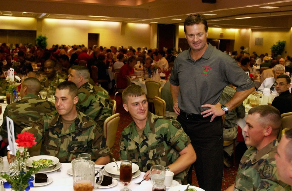 Photo - Lawton, OK,  Friday August 22, 2003:  (OU) University of Oklahoma head college football coach Bob Stoops took time out from his season to sign autographs and visit with troops and museum donors at Fort Sill.  Soldiers Nicholas Glover, Fort Wayne, IN., Luke Hortensteine, Rassey, IL.; and Christopher Willey, Dover, DE are greeted by Stoops.  Staff photo by Steve Sisney.