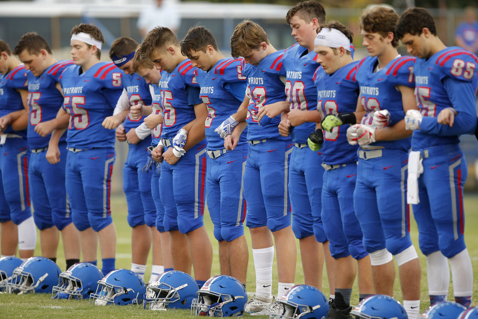 Photo - Southwest Covenant players lock arms during a moment of silence for Peter Webb before a football game between Southwest Covenant and Deer Creek-Lamont in Yukon, Okla., Friday, Oct. 4, 2019. Southwest Covenant hosted their first football game since the death of Peter Webb in September. [Bryan Terry/The Oklahoman]