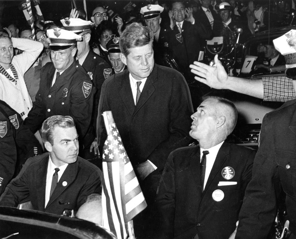 Photo - Democratic presidential nominee John F. Kennedy (center) chats with Oklahoma State Democratic Chairman Gene McGill (right) while Oklahoma Governor J. Howard Edmondson (left) listens during Sen. Kennedy's motorcade trip from Will Rogers Field to downtown Oklahoma City on Thursday night, 11/3/60.