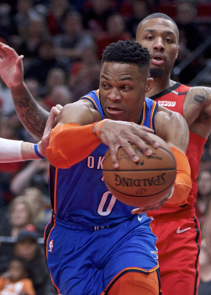 Photo - Oklahoma City Thunder guard Russell Westbrook looks to pass the ball in front of Portland Trail Blazers guard Damian Lillard during the first half of an NBA basketball game in Portland, Ore., Friday, Jan. 4, 2019. (AP Photo/Craig Mitchelldyer)