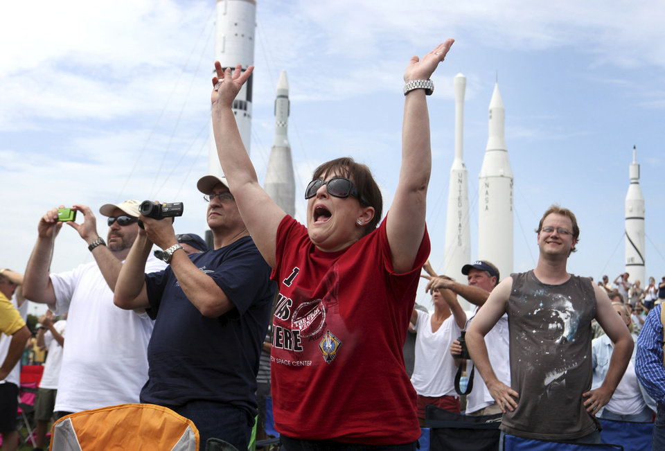 Photo -  FILE - In this July, 8, 2011 file photo, Vanessa Fabrega, of Austin, Texas, cheers as she and others watch the launch of space shuttle Atlantis from the Kennedy Space Center Visitor Complex in Cape Canaveral, Fla. Atlantis was the 135th and final shuttle launch for the U.S. (AP Photo/Julie Fletcher)