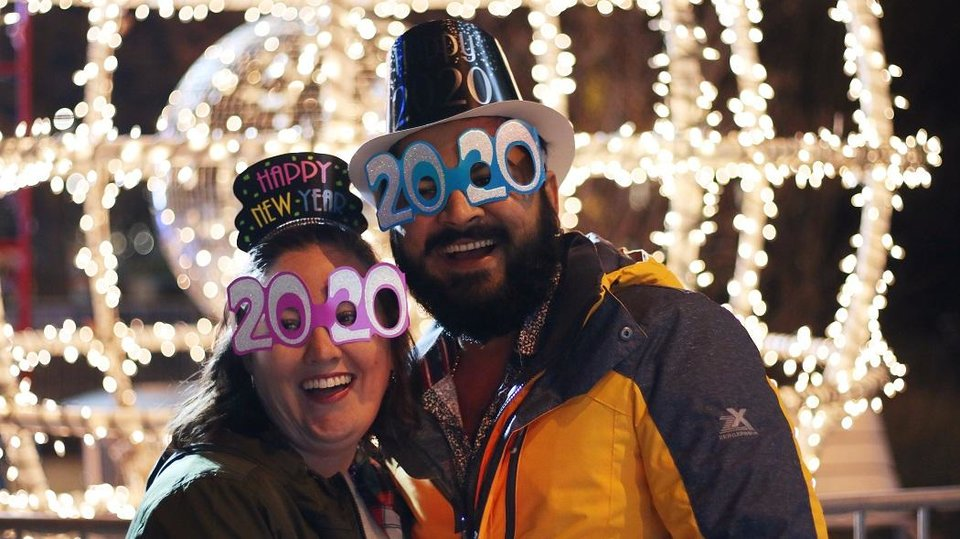 Photo - Jennifer Rich and Sam Patel pose in front of the ball in front of the Civic Center Music Hall during Opening Night downtown Oklahoma City, Tuesday, December 31, 2019. [Photo by Doug Hoke/The Oklahoman Archives]