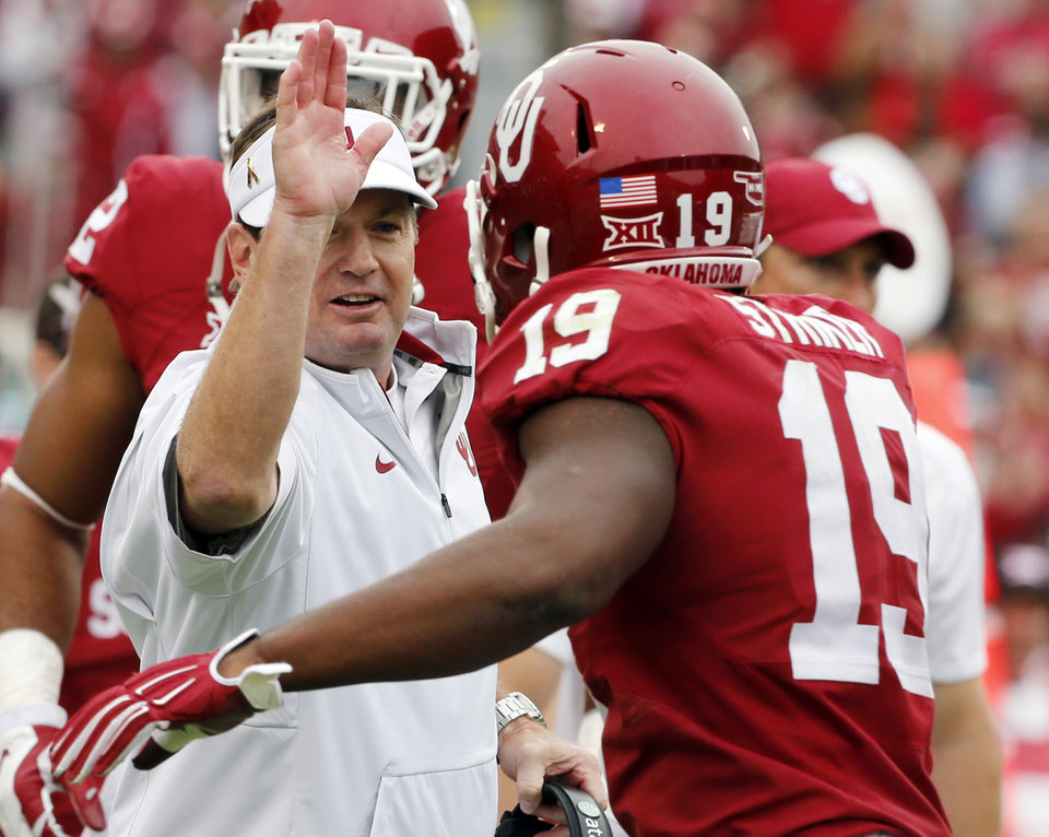 Photo - Oklahoma head coach Bob Stoops congratulates Oklahoma's Eric Striker (19) on an interception and score during a college football game between the University of Oklahoma Sooners (OU) and the Texas Tech Red Raiders at Gaylord Family-Oklahoma Memorial Stadium in Norman, Okla., on Saturday, Oct. 24, 2015. Photo by Steve Sisney, The Oklahoman