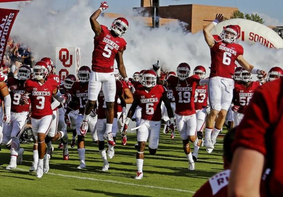 Photo -  Oklahoma's Baker Mayfield runs onto the field with the rest of the OU football team before a game against the Akron Zips at Gaylord Family — Oklahoma Memorial Stadium in Norman in September 2015. [Bryan Terry/The Oklahoman]