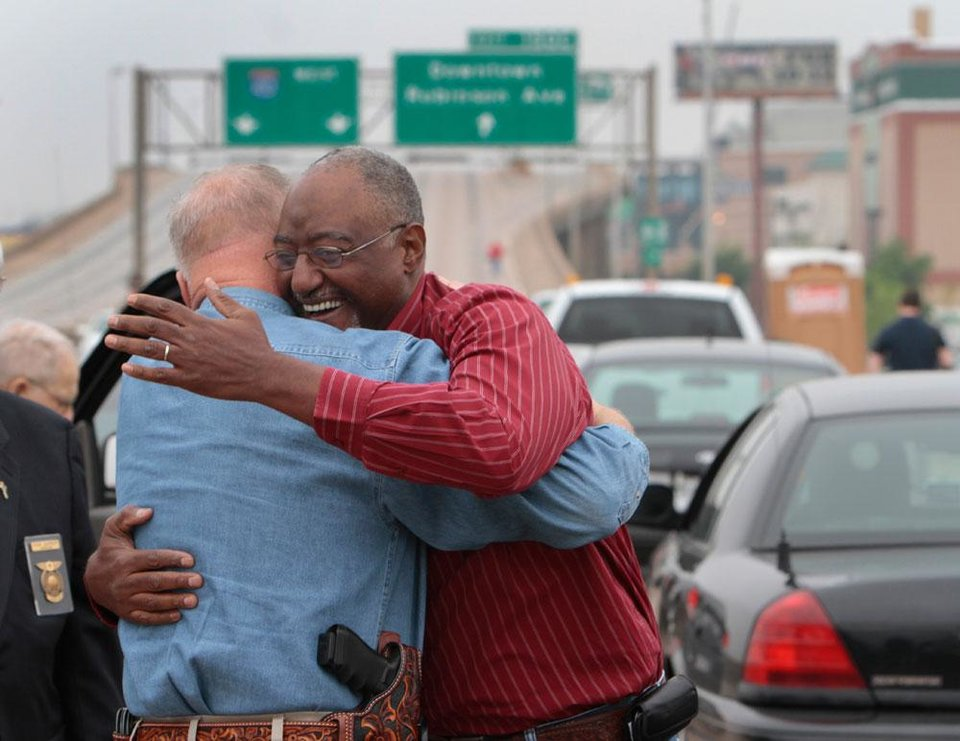 Photo -  Retired OHP Trooper Mark Crawford hugs his old lieutenant from the academy, Rodney Burris on the crosstown. OHP troopers past and present gather on old I-40 at Robinson to reminisce about the highway before this section is knocked down, Friday, April 6, 2012. Photo By David McDaniel, The Oklahoman