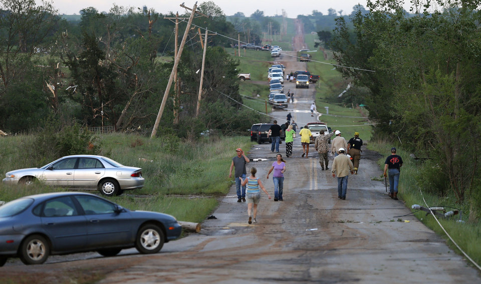 Photo - Residents walk down a street in Carney, Okla., after a tornado swept through the area on Sunday, May 19, 2013. Photo by Bryan Terry, The Oklahoman