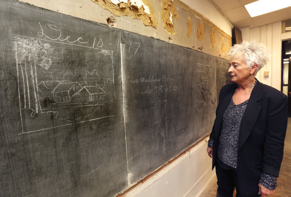 Photo - Principal Sherry Kishore looks at more historic blackboards covered up in 1917 which have just been uncovered in the 3rd floor classrooms at Emerson High School in Oklahoma City, OK, Friday, January 8, 2016,  Photo by Paul Hellstern, The Oklahoman