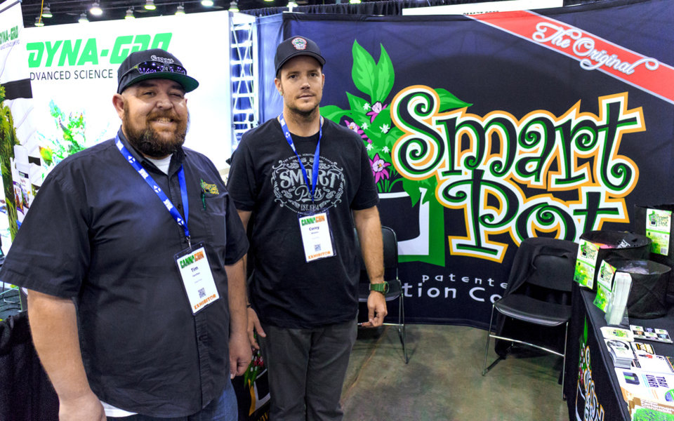 Photo - Tim Ferchau and Corey Rhames, from left, of Smart Pot, pose for a photo at their booth during the Oklahoma City CannaCon at the Cox Convention Center in Oklahoma City, Okla. on Wednesday, April 17, 2019.   Photo by Chris Landsberger, The Oklahoman