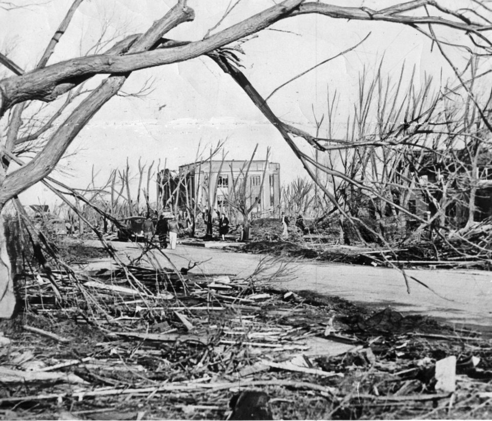 Photo - TORNADO DAMAGE: Bare tree limbs rise eerily as the damaged Woodward County courthouse stands in the background after a tornado struck April 9, 1947. The tornado killed 95 persons in Woodward, Okla. and covered parts of three states.