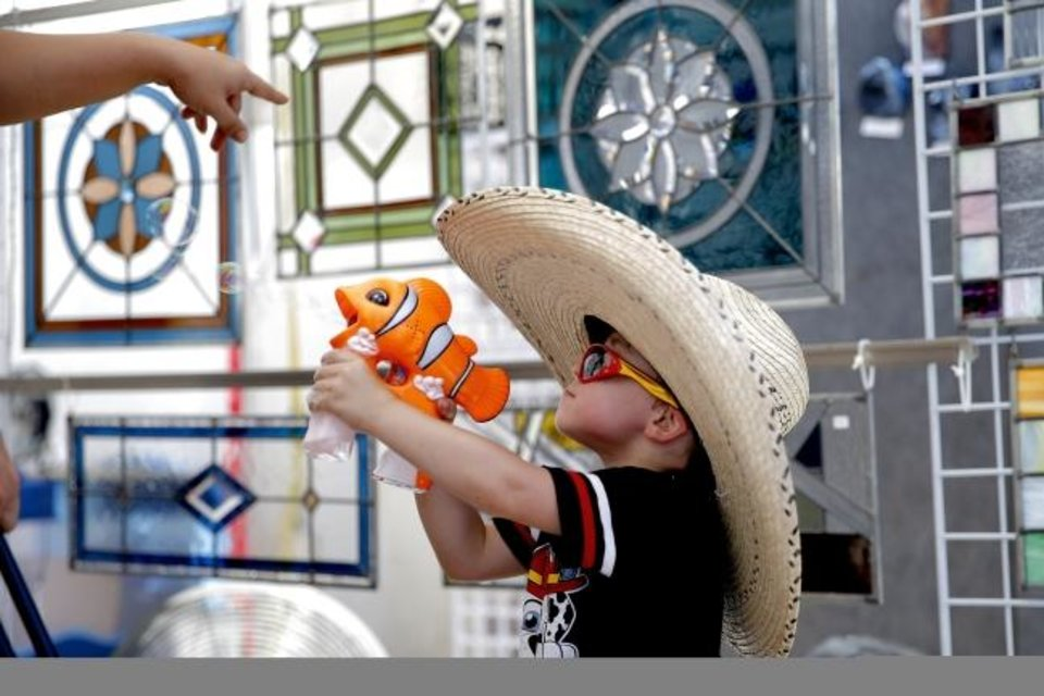 Photo -  Brogan Paul, 3, shoots bubbles inside the booth of artist Miki Oliver last year during the Paseo Arts Festival in Oklahoma City. [Bryan Terry/The Oklahoman Archives]