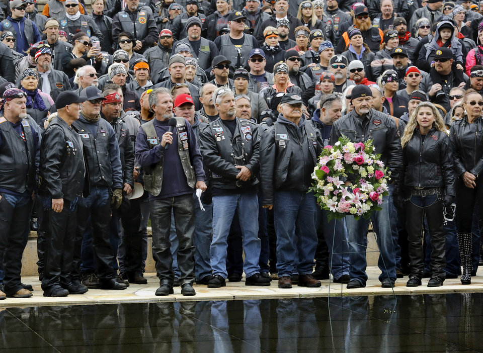 Photo - Willi Butler, a former Oklahoma City firefighter and co-organizer of the Ride to Remember, with microphone in his hand, speaks to participants as a wreath is placed beside the Reflecting Pool during a brief ceremony at the Oklahoma City National Memorial & Museum. Motorcyclists from across the country, numbering more than 1,000 strong, rumbled through the downtown streets of Oklahoma City on Saturday, April, 22, 2017,  taking part in  the 10th annual Ride to Remember.  The annual benefit run honors the 168 people killed in the April 19, 1995 bombing of the Alfred P. Murrah Federal Building. All funds raised go toward the Oklahoma City National Memorial and Museum, which operates solely on private donations. Bikers rolled out for the first event in 2007.    Photo by Jim Beckel, The Oklahoman