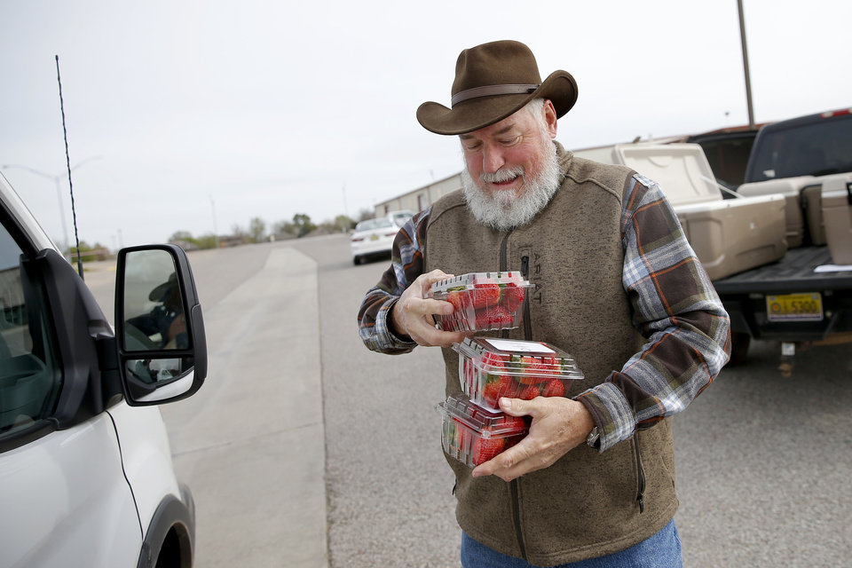Photo - Chris Willoughby with The Farm on Fishmarket brings an order to a customer at the Cleveland County Fairgrounds in Norman, Okla., Saturday, March 21, 2020. The weekly Norman Farm Market was closed to walk up business but customers were able to pick up orders placed in advance. [Bryan Terry/The Oklahoman]
