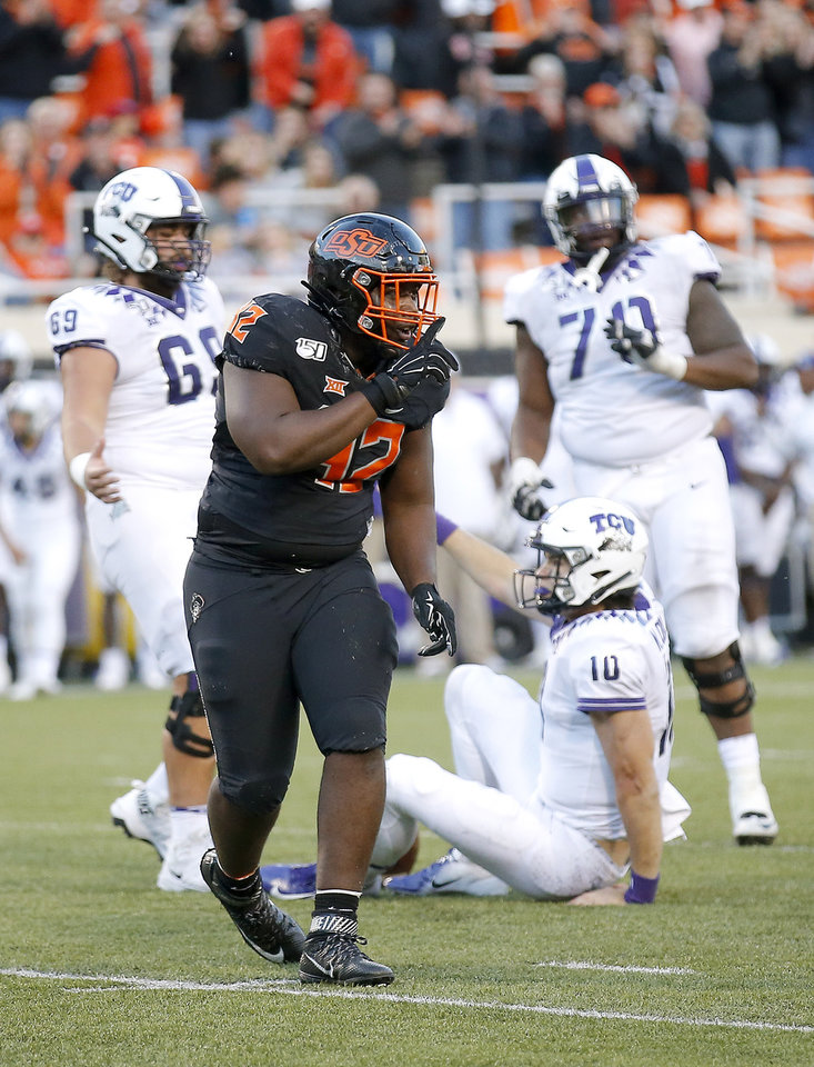 Photo - Oklahoma State's Jayden Jernigan (42) celebrates a sack on TCU's Mike Collins (10) in the fourth quarter during the college football game between the Oklahoma State University Cowboys and the TCU Horned Frogs at Boone Pickens Stadium in Stillwater, Okla.,  Saturday, Nov. 2, 2019. OSU won 34-27. [Sarah Phipps/The Oklahoman]