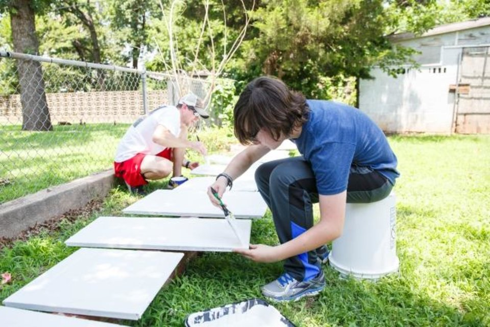 Photo -  Experts say those who help others were most likely to thrive. In 2018, Zachary Lane, paints panels of cabinets from a house that his United Methodist youth group is fixing up as part of a community service project in Oklahoma City.  [Oklahoman Archive Photo]