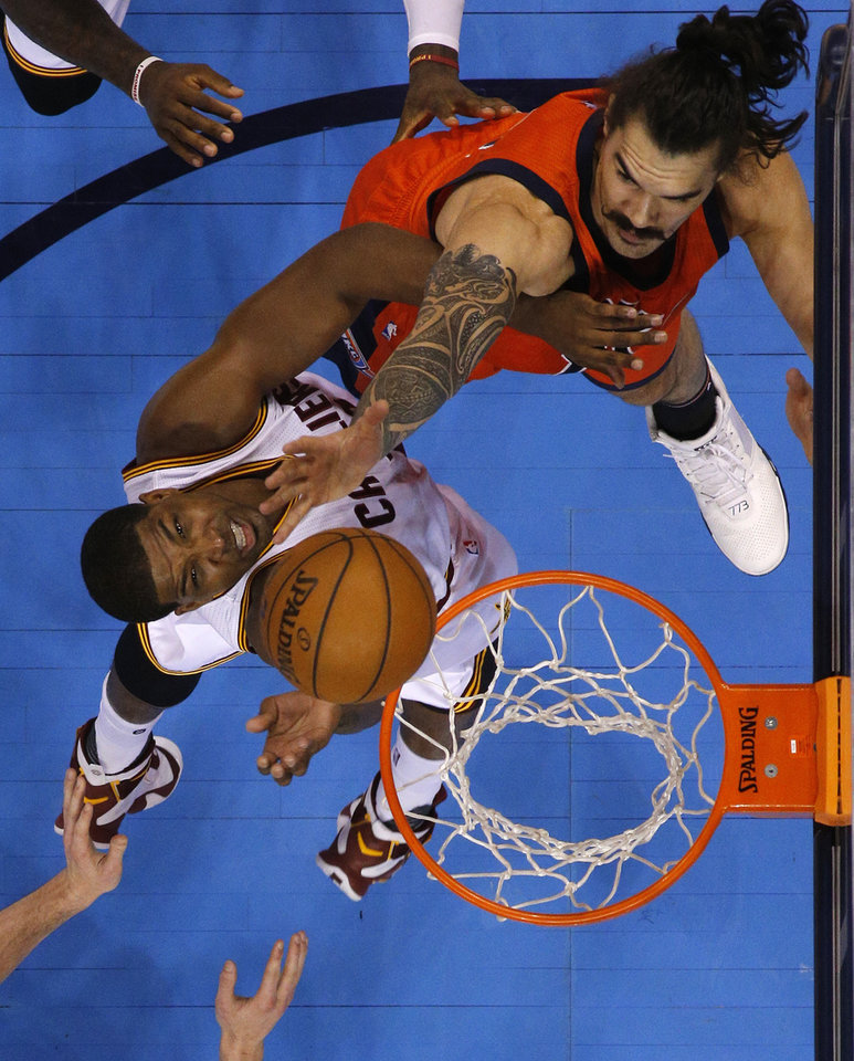 Photo - Cleveland's Tristan Thompson (13) grabs a rebound beside Oklahoma City's Steven Adams (12) during an NBA basketball game between the Oklahoma City Thunder and the Cleveland Cavaliers at Chesapeake Energy Arena in Oklahoma City, Sunday, Feb. 21, 2016. Oklahoma City lost 115-92.  Photo by Bryan Terry, The Oklahoman