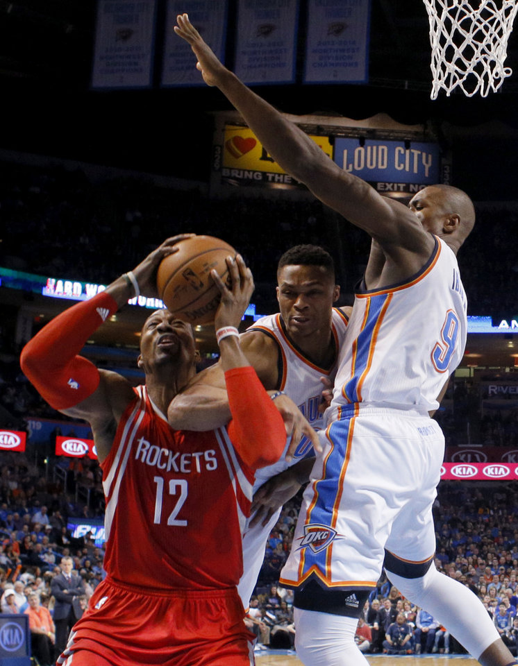 Photo - Houston's Dwight Howard (12) is fouled by Oklahoma City's Russell Westbrook (0) as Serge Ibaka (9) helps defend during an NBA basketball game between the Oklahoma City Thunder and the Houston Rockets at Chesapeake Energy Arena in Oklahoma City, Friday, Jan. 29, 2016. Oklahoma City won 116-108. Photo by Bryan Terry, The Oklahoman