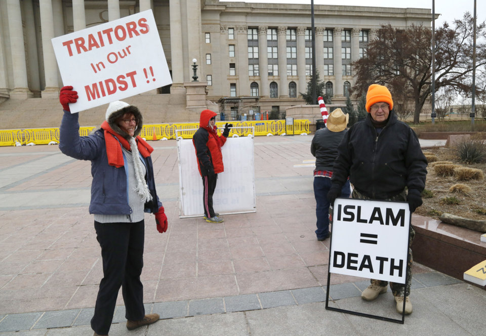 Photo - Protestors wave signs in disapproval as CAIR and local Muslims gather at the State Capitol in Oklahoma City, OK, for Oklahoma Muslim Day, Friday, February 27, 2015,  Photo by Paul Hellstern, The Oklahoman