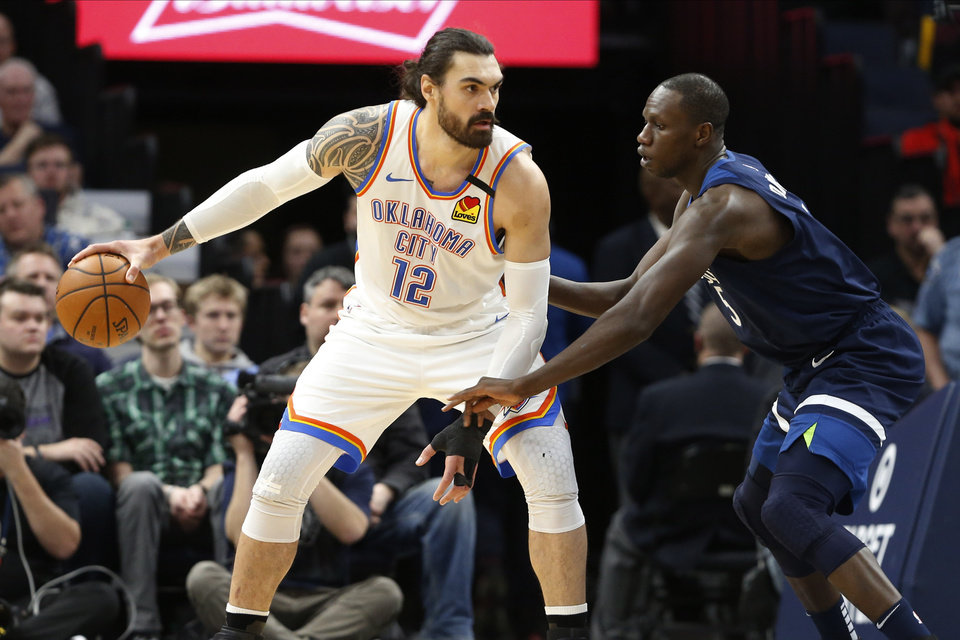 Photo - Oklahoma City Thunder's Steven Adams, left, of New Zealand keeps the ball at arms length form Minnesota Timberwolves' Gorgui Dieng, of Senegal, in the first half of an NBA basketball game Monday, Jan. 13, 2020, in Minneapolis. (AP Photo/Jim Mone)
