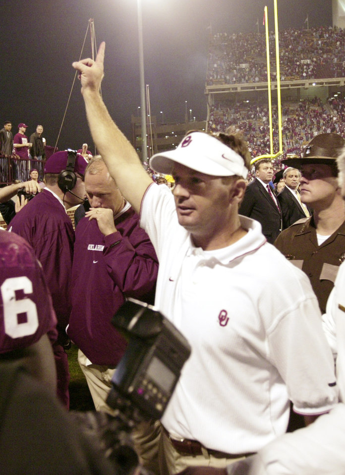 Photo - OSU vs OU (UNIVERSITY OF OKLAHOMA, OKLAHOMA STATE UNIVERSITY) Bedlam college football at Gaylord Family - Oklahoma Memorial Stadium, Saturday, Nov 1, 2003 in Norman, Ok.  OU head coach Bob Stoops flashes the No. 1 sign to fans as he leaves the field.  Staff photo by Doug Hoke.