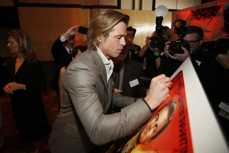 Photo - Brad Pitt signs a poster at the 92nd Academy Awards Nominees Luncheon at the Loews Hotel on Monday, Jan. 27, 2020, in Los Angeles. [Photo by Danny Moloshok/Invision/AP]