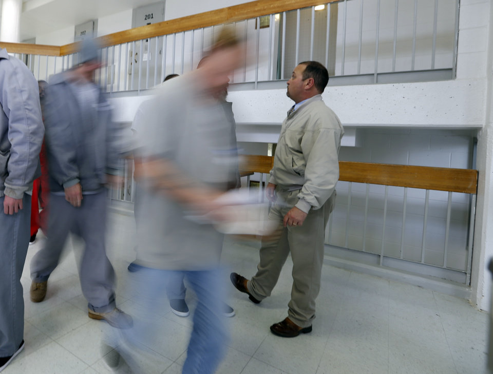 Photo - Inmates head to lunch inside the mental health unit at Joseph Harp Correctional Center on Feb. 23, 2016 in Lexington, Okla. Warden Carl Bear is at right.  Photo by Steve Sisney, The Oklahoman