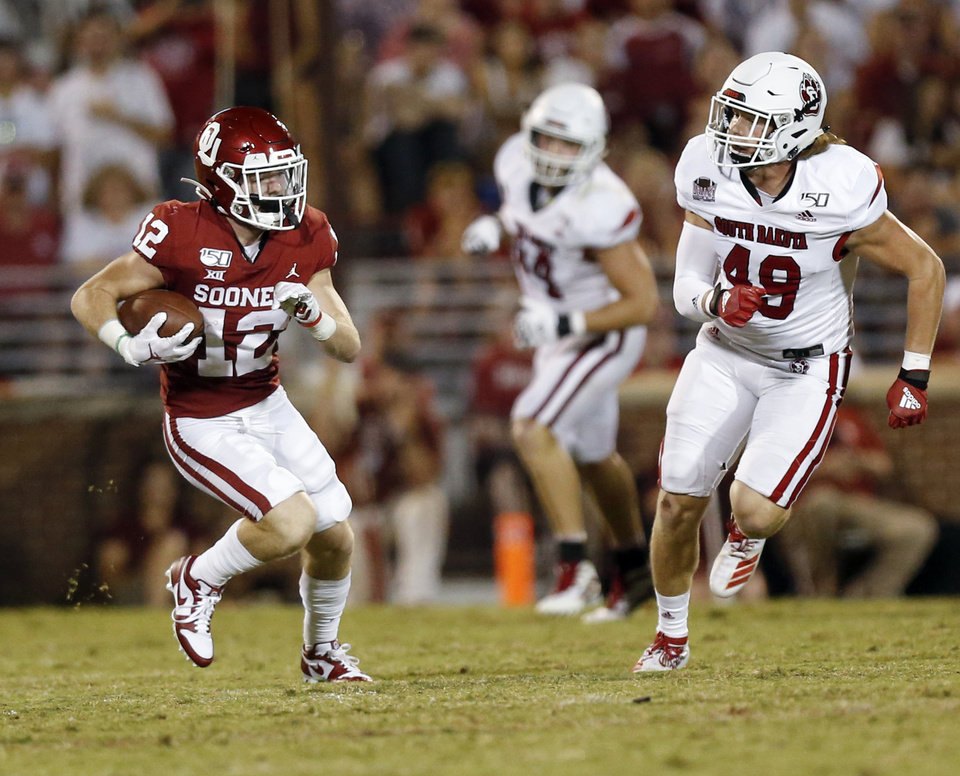 Photo - Oklahoma's Drake Stoops (12) runs after a catch near South Dakota's Brock Mogensen (49) in the third quarter during a college football game between the Oklahoma Sooners (OU) and South Dakota Coyotes at Gaylord Family - Oklahoma Memorial Stadium in Norman, Okla., Saturday, Sept. 7, 2019. [Nate Billings/The Oklahoman]