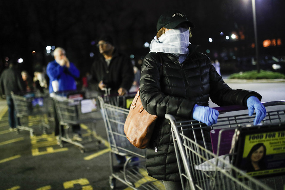 Photo -  Customers wearing protective masks and gloves wait in line, Friday, at a Stop & Shop supermarket that opened special morning hours to serve people 60-years and older due to coronavirus concerns, in Teaneck, N.J. [John Minchillo/The Associated Press]