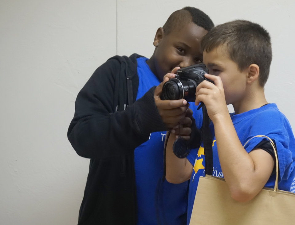 Photo - Brandon, age 9, and Antonio, age 10, continue to utilize their newfound photography skills at the Nature Conservancy's reception on Tuesday.