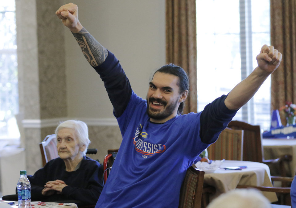 Photo - Oklahoma City Thunder's Steven Adams celebrates after a resident won a game of bingo at Brookdale Village, a senior living community in Oklahoma City, Monday November, 29 2016. Seated next to Adams is Billie Burget. Thunder players Alex Abrines, Steven Adams, Enes Kanter and Andre Roberson played bingo with residents. Photo By Steve Gooch, The Oklahoman