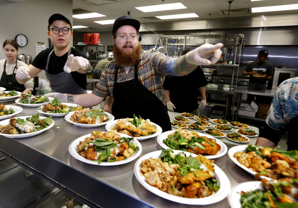 Photo -  Paul Wang and Derek Forari direct the serving line at the Homeless Alliance on April 17 in Oklahoma City. [Photo by Steve Sisney, The Oklahoman]