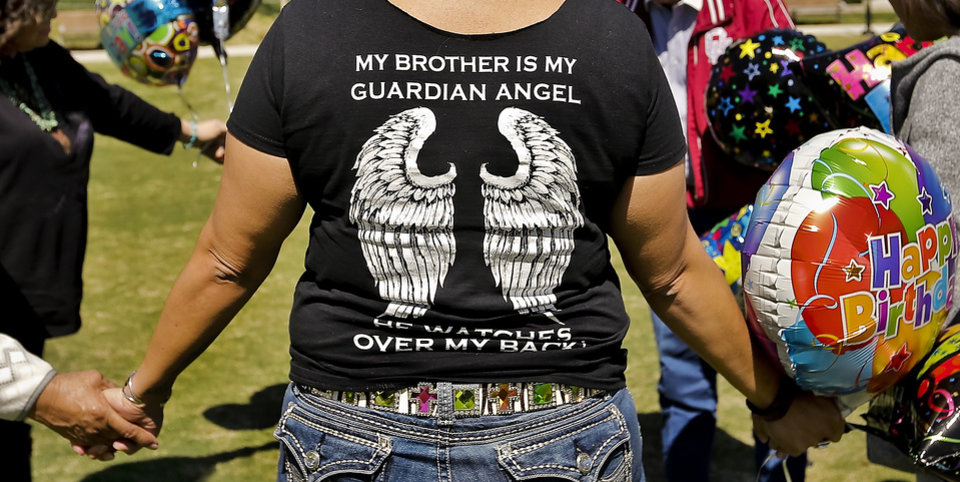 Photo - Melissa Wahnee wears a shirt in honor of her brother as family members gather in prayer before releasing balloons in honor of Bradley Wahnee, who was killed in 2009 during a drive by shooting, to mark his birthday at the Myriad Botanical Gardens in Oklahoma City, Okla. on Monday, March 21, 2016. The family releases balloons every year on Bradley's birthday and the date he was killed.  Photo by Chris Landsberger, The Oklahoman