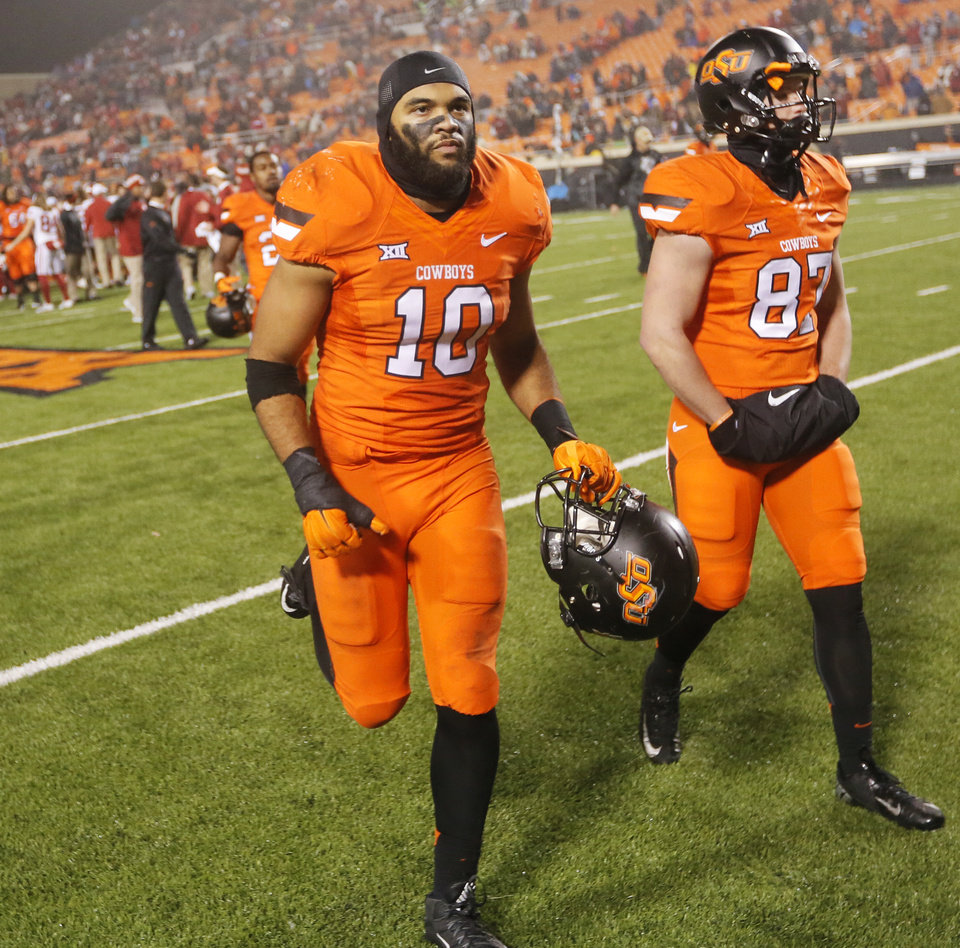 Photo - Oklahoma State's Seth Jacobs (10) and Grant Newell (87) leave the field after the Bedlam college football game between the Oklahoma State Cowboys (OSU) and the University of Oklahoma Sooners (OU) at Boone Pickens Stadium in Stillwater, Okla., Saturday, Nov. 28, 2015. OU won 58-23. Photo by Nate Billings, The Oklahoman