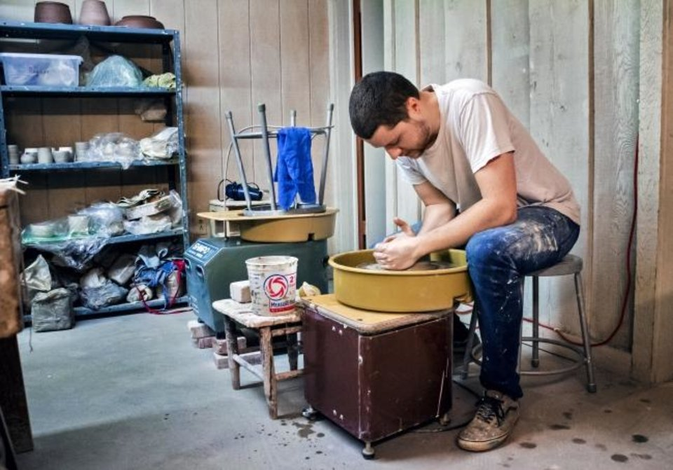 Photo -  Taylor Dickerson works with clay as he creates a vase at The House of Clay.   [Chris Landsberger/The Oklahoman]