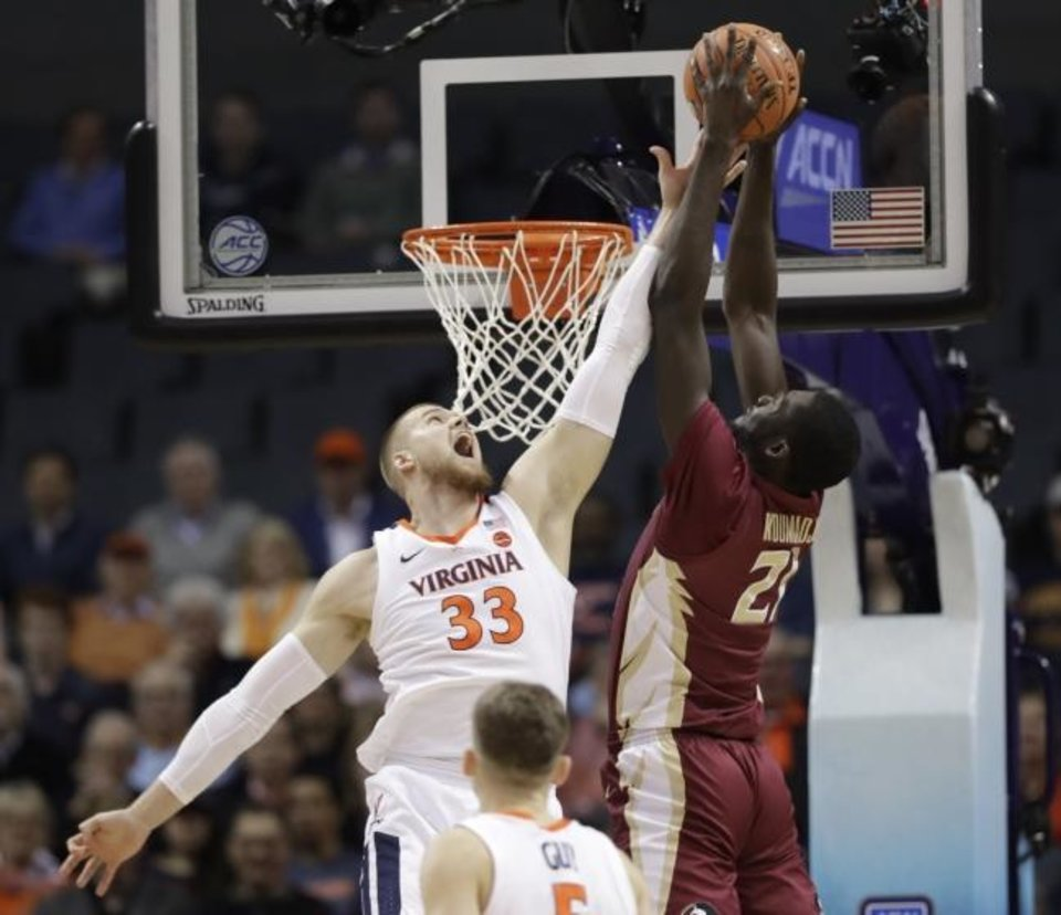 Photo -  Florida State's Christ Koumadje (21) tries to dunk over Virginia's Jack Salt (33) during the ACC Tournament last weekend. [AP Photo/Chuck Burton]