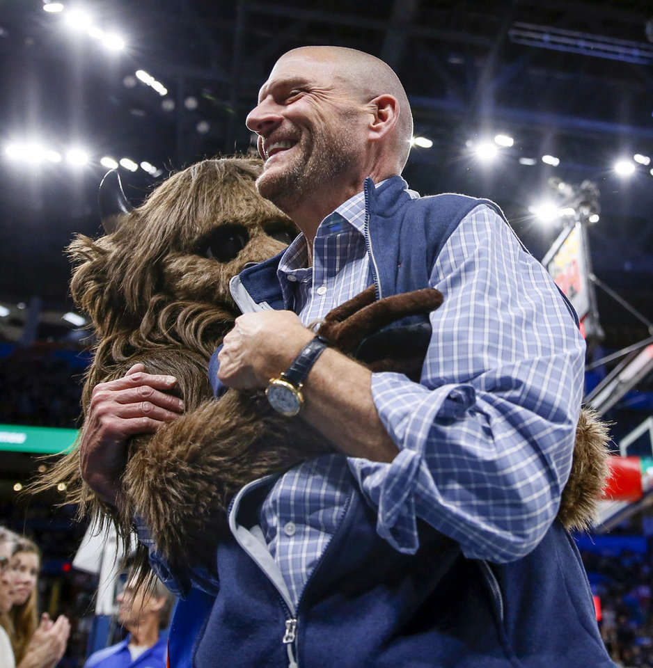 Photo - Clay Bennett gets a hug from mascot Rumble the Bison during an NBA basketball game between the Oklahoma City Thunder and the Washington Wizards at Chesapeake Energy Arena in Oklahoma City, Friday, Oct. 25, 2019. The Wizards won 97-85. [Nate Billings/The Oklahoman]