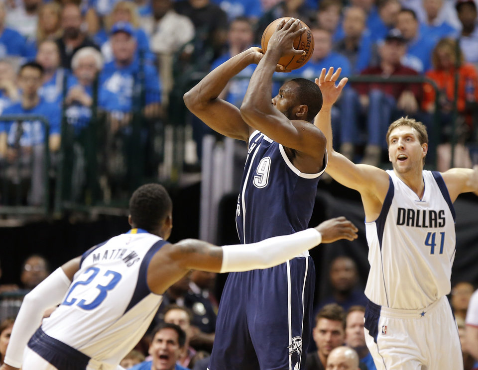 Photo - Oklahoma City's Serge Ibaka (9) puts up a shot between Dallas' Wesley Matthews (23) and Dirk Nowitzki (41) during Game 3 of the first round series between the Oklahoma City Thunder and the Dallas Mavericks in the NBA playoffs at American Airlines Center in Dallas, Thursday, April 21, 2016. The Thunder won 131-102. Photo by Bryan Terry, The Oklahoman