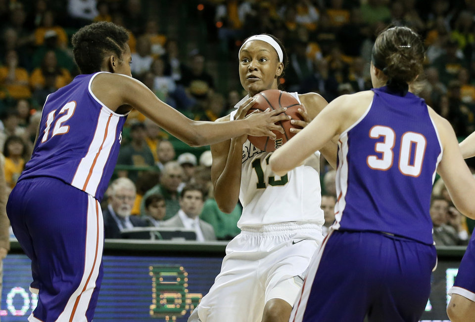 Photo - Northwestern State 's Chelsea Rogers (12) and Beatrice Attura (30) attempt to stop a drive to the basket by Baylor's Nina Davis, center, in the second half of a women's college basketball game in the first round of the NCAA tournament Friday, March 20, 2015, in Waco, Texas. Baylor won 77-36.  (AP Photo/Tony Gutierrez)