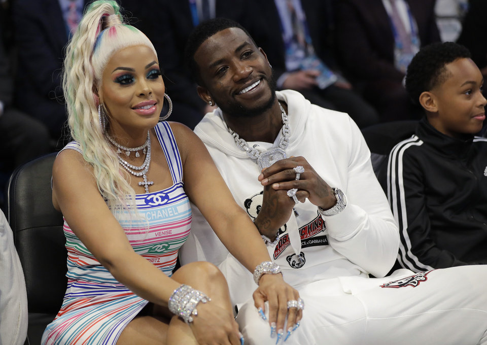 Photo - Rapper Gucci Mane, right sits with his wife Keyshia Ka'Oir during the first half of an NBA All-Star basketball game, Sunday, Feb. 17, 2019, in Charlotte, N.C. (AP Photo/Chuck Burton)