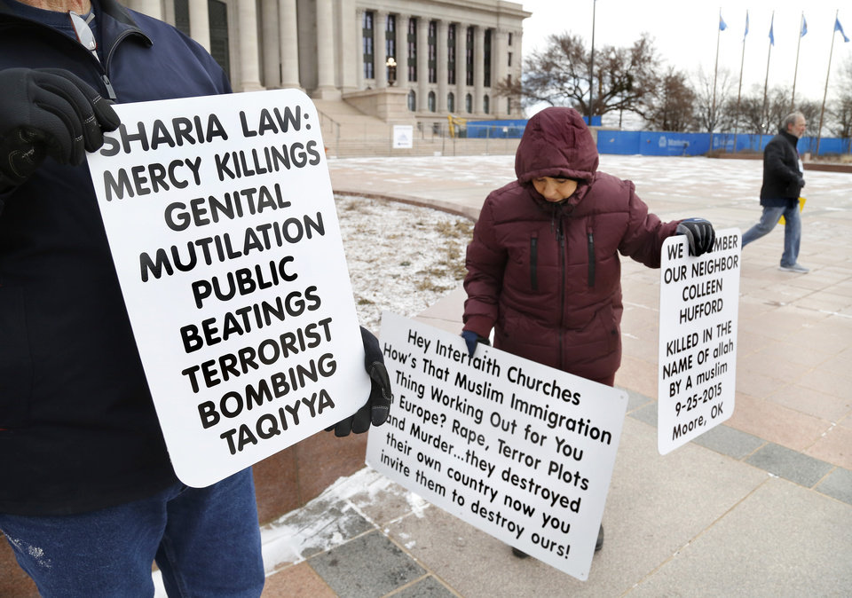 Photo - A man walking across the south plaza at the Capitol to welcome Muslim visitors is countered by a man and a woman holding signs critical of the Islam faith.  More than 100 participated in Muslim Day at the Capitol on Monday, March 4, 2019.  The annual event is sponsored by the Council on American-Islamic Relations-Oklahoma chapter. Interfaith supporters   held signs welcoming Muslim guests as they arrived at the Capitol. A man and a woman stood nearby, displaying placards expressing concerns about crimes committed by some Muslims in the recent past.   Photo by Jim Beckel, The Oklahoman.