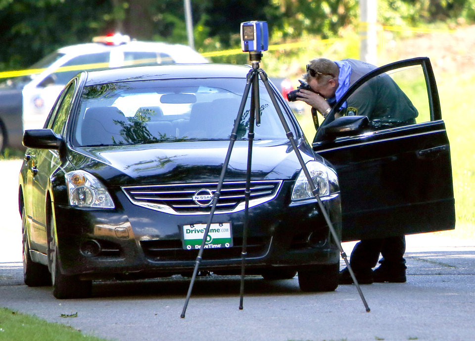 Photo -  An investigator photographs the inside of a car on June 20, 2016 at the scene of a double homicide near NE 15th and Highland in Oklahoma City. [The Oklahoman Archives]