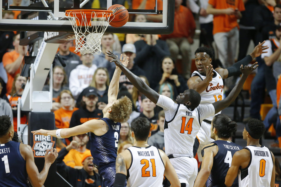 Photo - Georgetown's Mac McClung (2) is fouled by Oklahoma State's Yor Anei (14) as he akes a basket during a college basketball game between the Oklahoma State University Cowboys (OSU) and the Georgetown Hoyas at Gallagher-Iba Arena in Stillwater, Okla., Wednesday, Dec. 4, 2019. Georgetown won 84-71. [Bryan Terry/The Oklahoman]