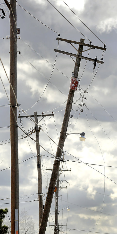 Photo - Police and firefighters closed a section of NW 36 Street near N. Utah,  Wednesday afternoon, March 13, 2019, after high southerly winds caused this utility pole on NW 36 to sway back and forth above the road. Firefighters reported arcing wires on the next pole to this one. Photo by Jim Beckel, The Oklahoman.