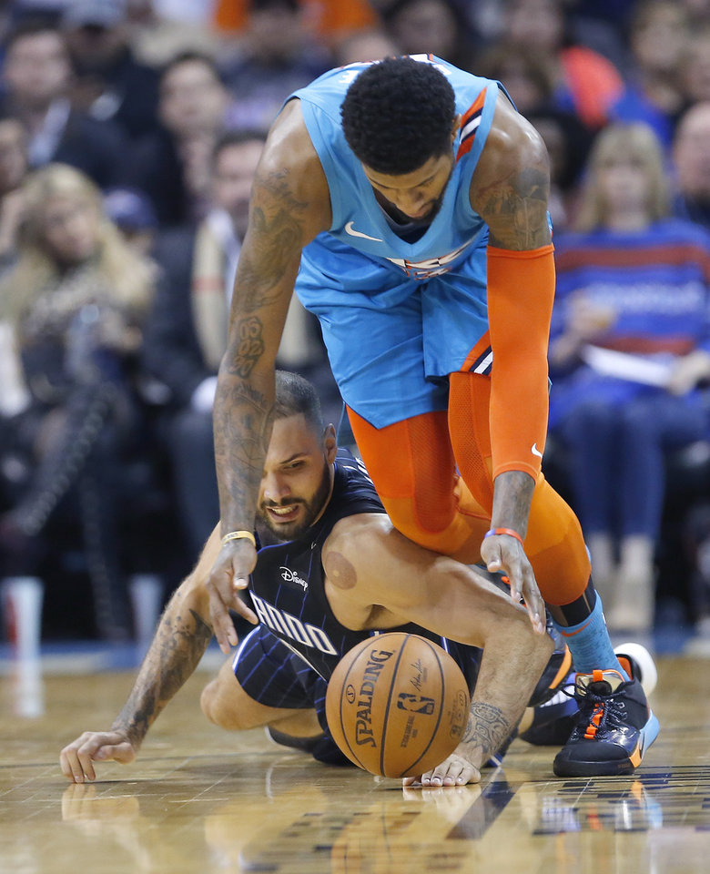 Photo - Oklahoma City's Paul George (13) and Orlando's Evan Fournier (10) scramble for a loose ball during the NBA game between the Oklahoma City Thunder and the Orlando Magic at the Chesapeake Energy Arena  Tuesday, Feb. 5, 2019. Photo by Sarah Phipps, The Oklahoman