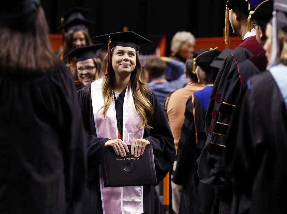 Photo - Graduates pass by their professors after receiving their diplomas during the Undergraduate Commencement Ceremony for the College of Human Sciences and the College of Engineering, Architecture & Technology at the Gallagher-Iba Arena on the campus of Oklahoma State University in Stillwater, Okla. Saturday, May 13, 2017.  Photo by Paul Hellstern, The Oklahoman