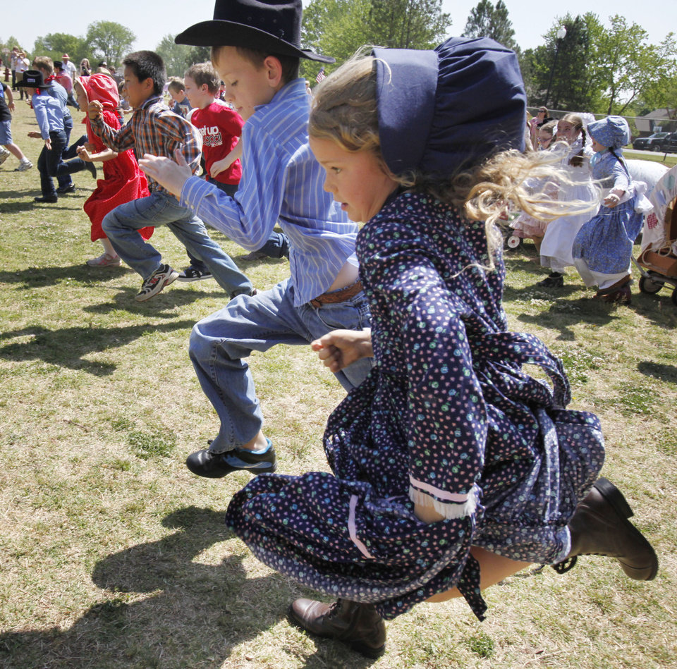 Photo - Children run across the playground to stake their claim during a land run re-enactment at Chisholm Elementary School in Edmond, OK, Friday, April 22, 2011. By Paul Hellstern, The Oklahoman