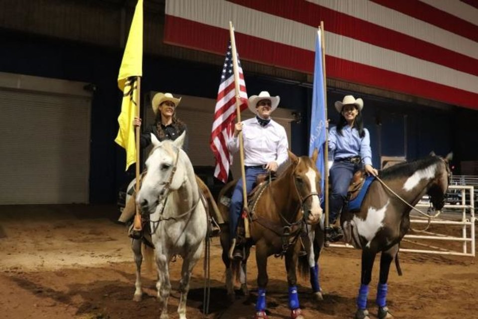 Photo -  Lori Campbell of Arnett, a member of the Oklahoma Cattlemen's Association, presents colors before the start of the association's Ranch Rodeo event with Oklahoma Gov. Kevin Stitt and Agriculture Secretary Blayne Arthur. [PROVIDED BY OKLAHOMA CATTLEMEN'S ASSOCIATION]