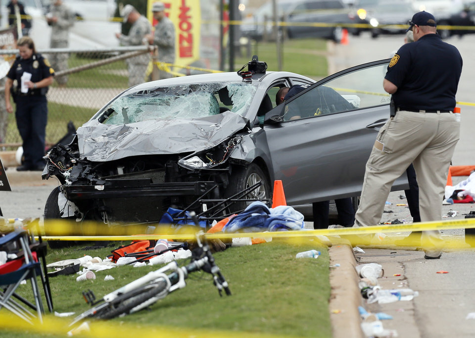 Photo - Law enforcement officers investigate a fatal crash at the intersection of Main and Hall of Fame during the Oklahoma State University (OSU) homecoming parade in Stillwater, Okla., Saturday, Oct. 24, 2015. Photo by Nate Billings, The Oklahoman